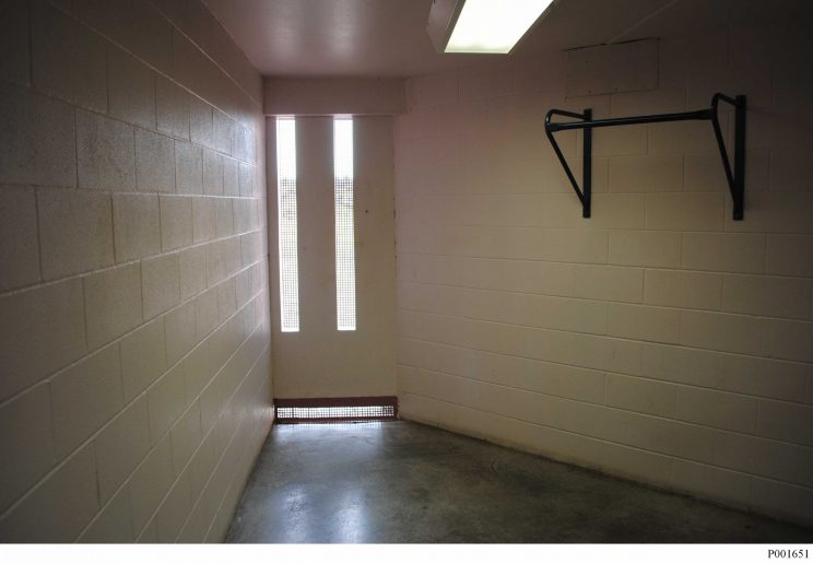 A cinderblock room with walls that narrow toward the far end from approximately 8 feet wide near the photographer to approximately 3 feet wide at the far end. At the end, there are two long narrow windows extending from about one foot off the floor to about 6 inches from the ceiling. The room is empty except for a flourescent light on the ceiling and a chin-up bar on the right wall.