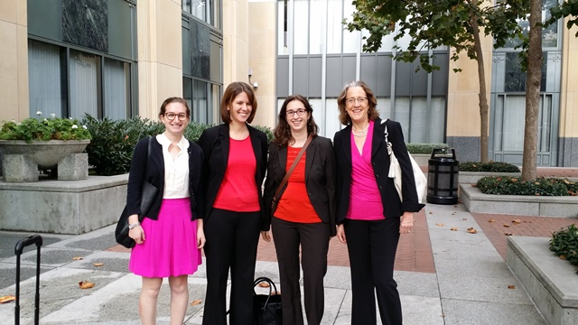 Image:  four of the women from the photo above, wearing, from left to right. a pink skir with black jacket, a black suit with a red shirt, another in a black suit with a red shirt, and finally a black suit with a pink shirt.