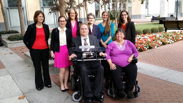 Image:  eight people posing for a photo in front of foliage.  Six women stand in the back row; in the front, a man in a wheelchair and a woman in a wheelchair.