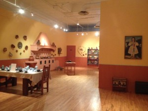 Photo of museum space with high ceilings, open rooms and painted warm colors of yellow and orange. In the foreground, a table.