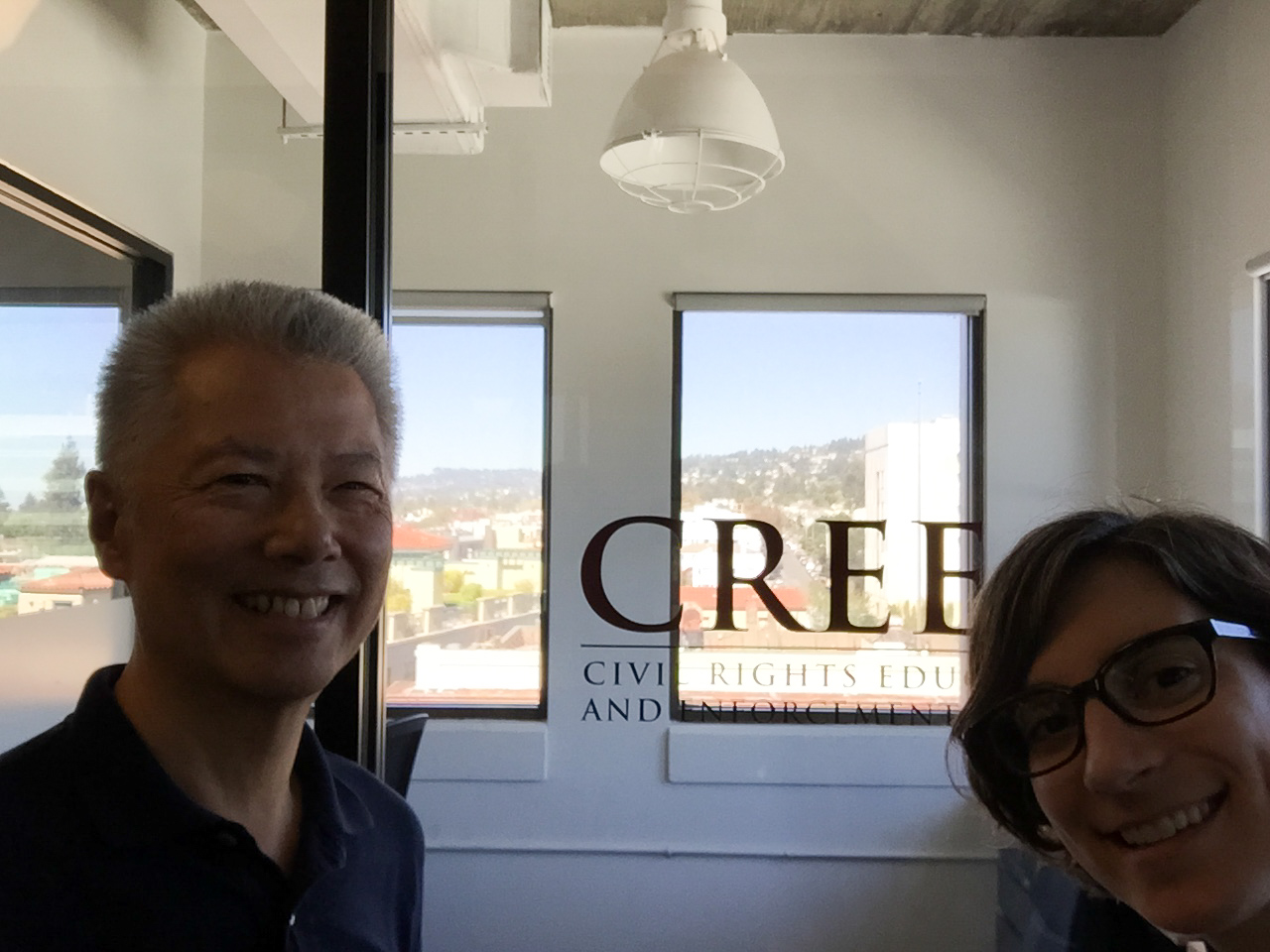 Image:  Same glass window with CREEC logo, but with two people peeking into the photo from the left and right.  On the left, an Asian man; on the right a white woman.