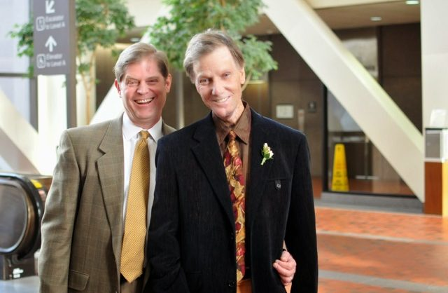 Photo of two white men in jackets and ties.