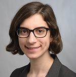 Image: photo/headshot of white woman with brown hair and glasses wearing a suit jacket and green shirt.