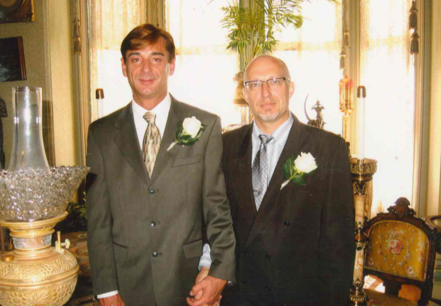 Two men standing with hands clasped, both wearing formal suits