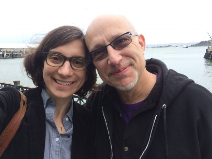 Woman in glasses and man in sunglasses lean their heads together and smile in selfie.