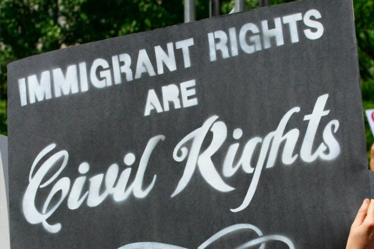 """a hand holds a black sign with white chalk text: """"immigrant rights are civil rights"""""""