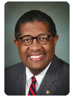 Image: portrait photo of African American man with glasses wearing a suit jacket and tie.