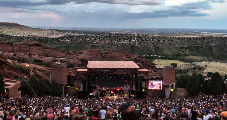 Image: photo of an outdoor amphitheater shot from the back row with the audience between the camera and the stage, with the foothills of Colorado in the background.
