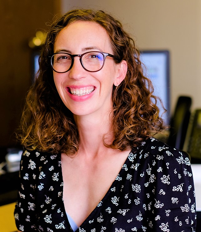 Image: Liz Jordan, white woman with glasses and curly hair, smiling