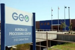 Photograph of the sign outside GEO Aurora ICE Processing Center. The Detention center is blurry in the background.