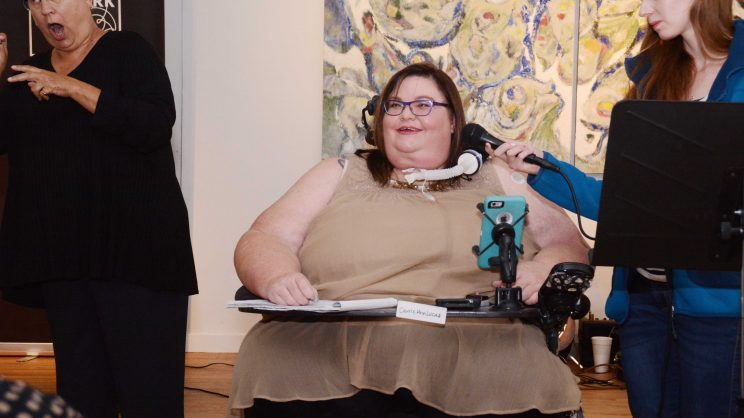 Image: Carrie Ann Lucas, light skinned Latina woman of size with mid-length brown hair, wearing a beige blouse and dark skirt. She is speaking into a mic held for her by a white woman with red hair. To the left, a woman dressed entirely in black interprets into ASL.