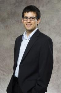 Image of Cesar, a man standing in a dark blazer.