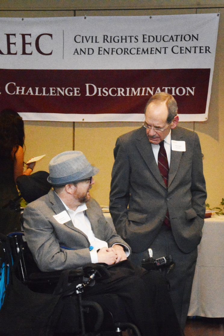 Two men talking. One is standing and one is seated in a wheelchair.