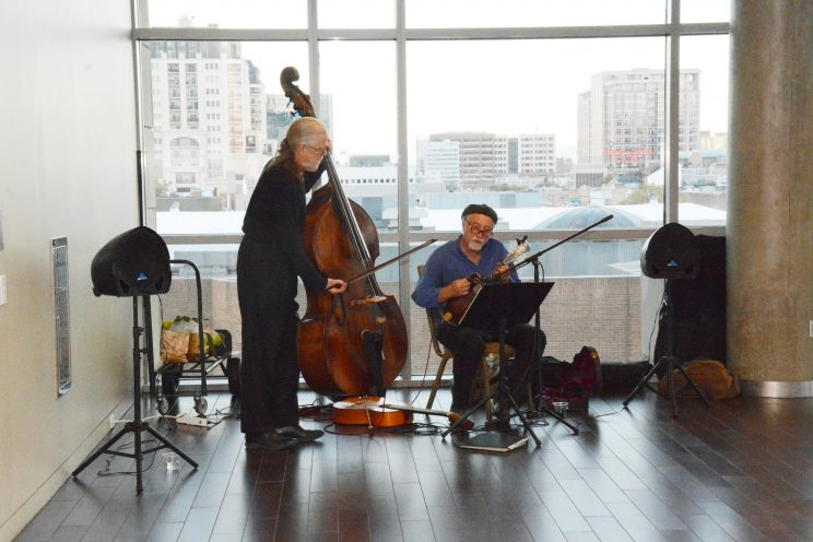 Image of musicians playing standup bass and smaller string instrument in front of large windows showcasing Downtown Denver.