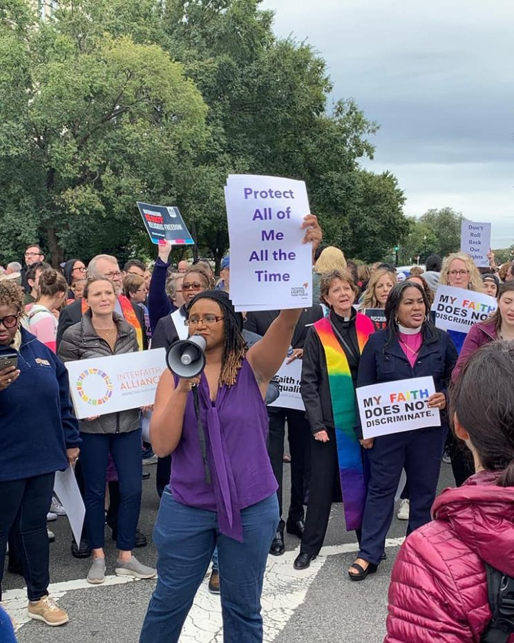 """group of protesters at a rally. Woman in foreground is talking into a megaphone and holding a sign that reads, """"Protect All of Me All the Time"""". Women in the background are holding signs that say, """"My Failth Does Not Discriminate."""""""
