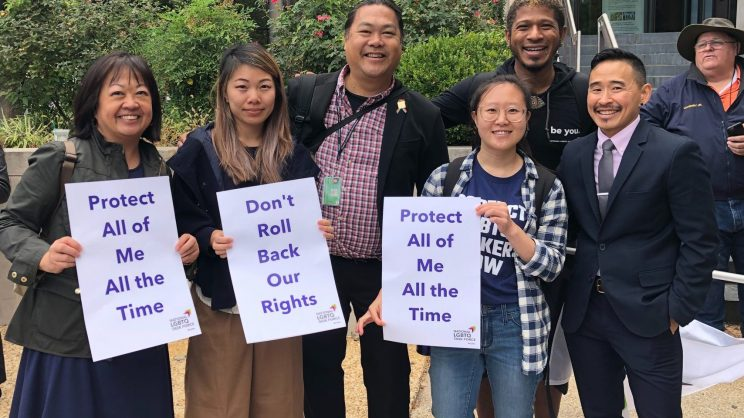 """Group of protesters at a rally holding signs that read """"Protect All of Me All the Time"""" and, """"Don't Roll Back Our Rights"""""""