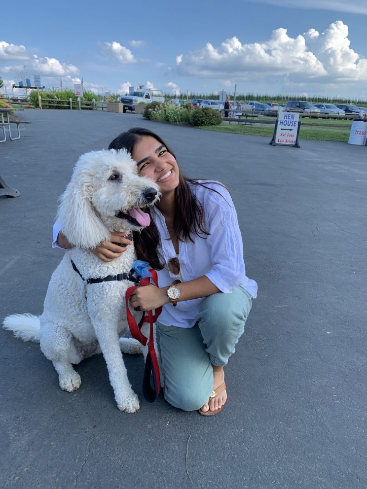 Parima Kadikar is kneeling next to and hugging her dog (a white labradoodle) in a parking lot. Parima is wearing jeans, sandals and a purple oxford shirt.