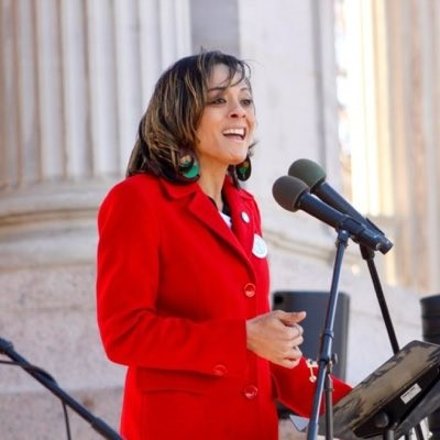 Elisabeth Epps is standing in front of a microphone giving a speech. She is wearing a red blazer.