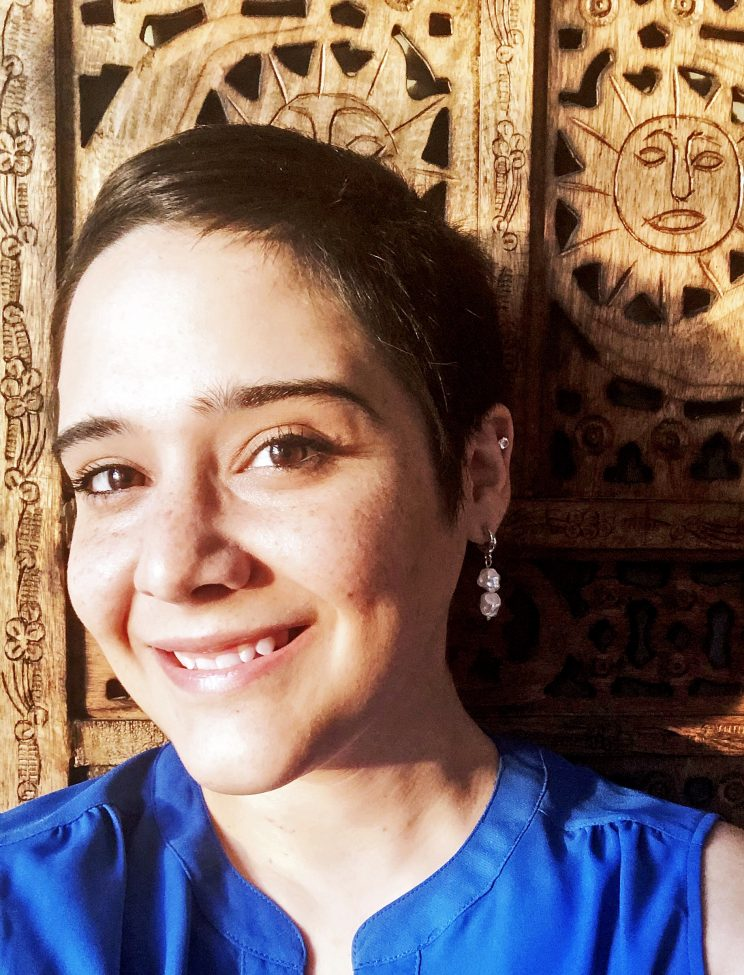 Anne-Marie is looking into the camera and smiling. The background is a wooden screen with suns carved into it. She has brown eyes and short brown hair.