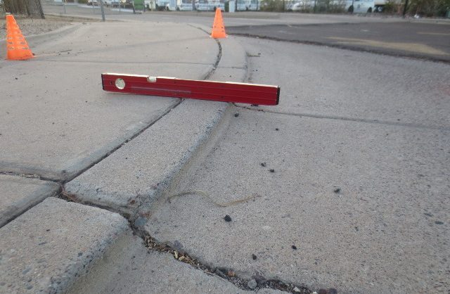 close up of a builder's level showing an unsafe curb ramp access point and a large crack