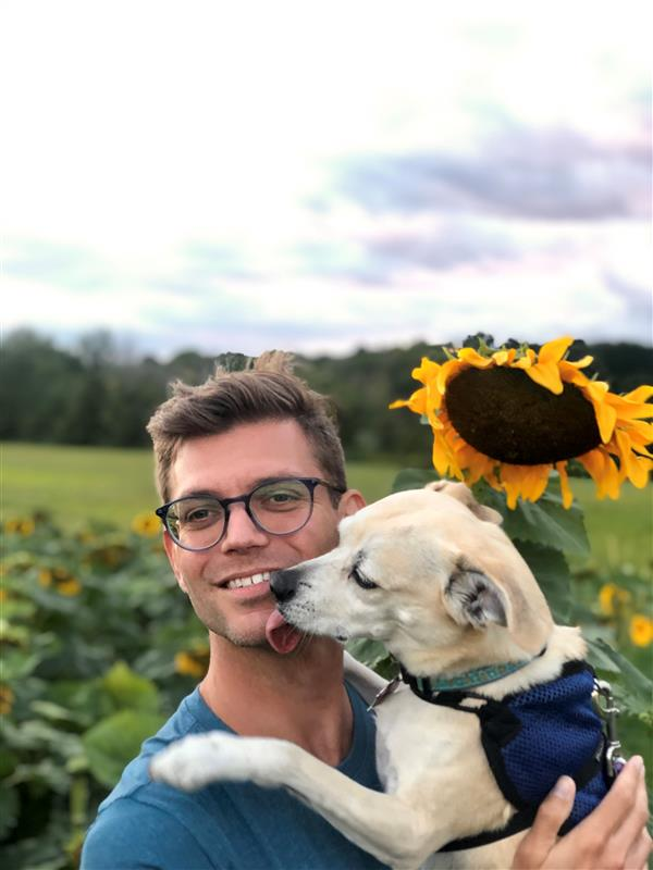 Man holding dog in front of sunflower