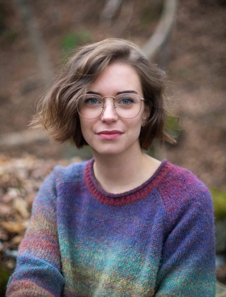 Person with glasses and short brown hair wearing a multicolored sweater outdoors.