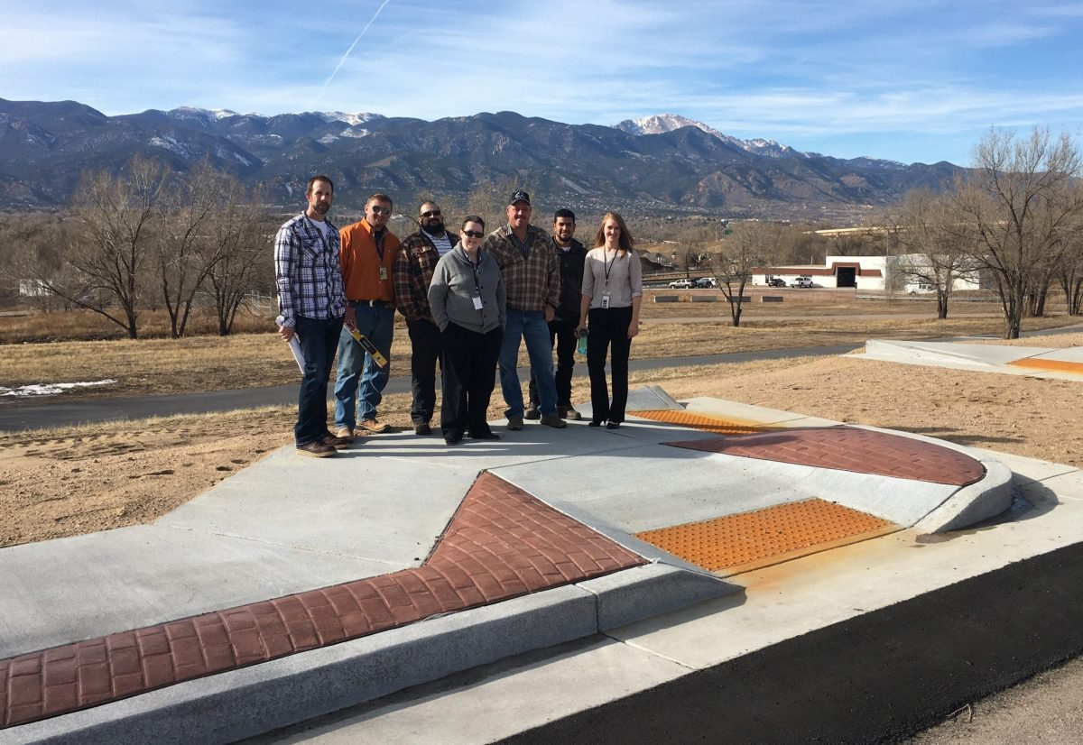 Photograph of seven individuals, including CREEC staff member Martie Lafferty and Colorado Springs city staff, standing on pavement in front of mountains. The pavement has a large brick and concrete curb with an on-ramp and textured area.