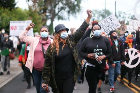 Photograph of a protest with three individuals in the center of the photo. They are Black, feminine-presenting individuals wearing face masks.