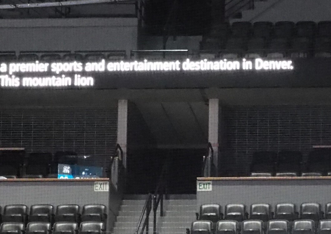 """Empty stadium seats with LED banner with captions. Words read, """"a premier sports and entertainment destination in Denver. This mountain lion"""""""