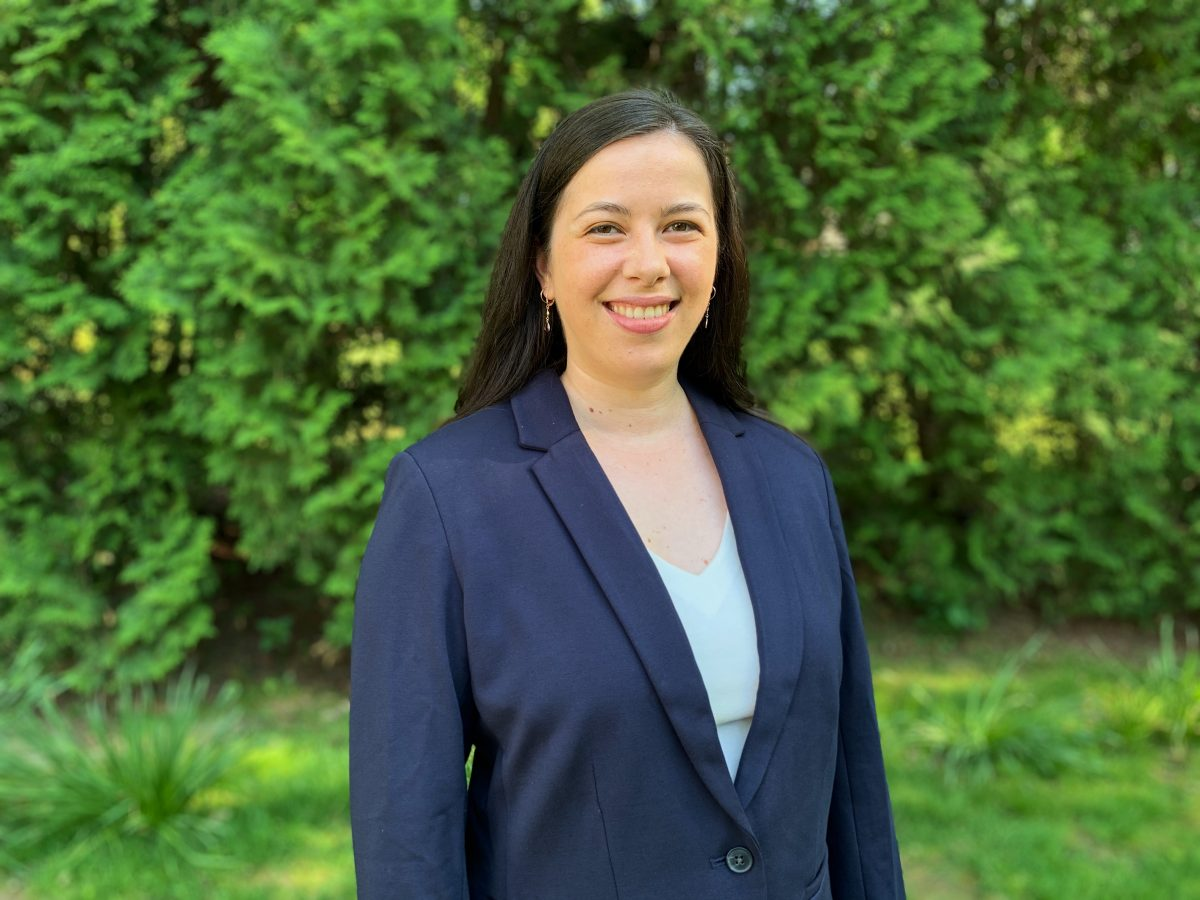 Photograph of Ruby. Ruby is a light skinned person with long dark hair. She is wearing a navy blazer with a pale blue shirt underneath. She is smiling and standing in front of a wall of green trees.