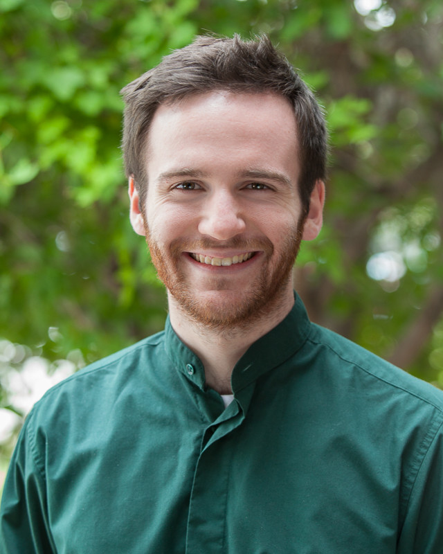 Photo of Sam, a person with pale skin, short brown hair, and a short brown beard. They are wearing a dark green button-up shirt and smiling.
