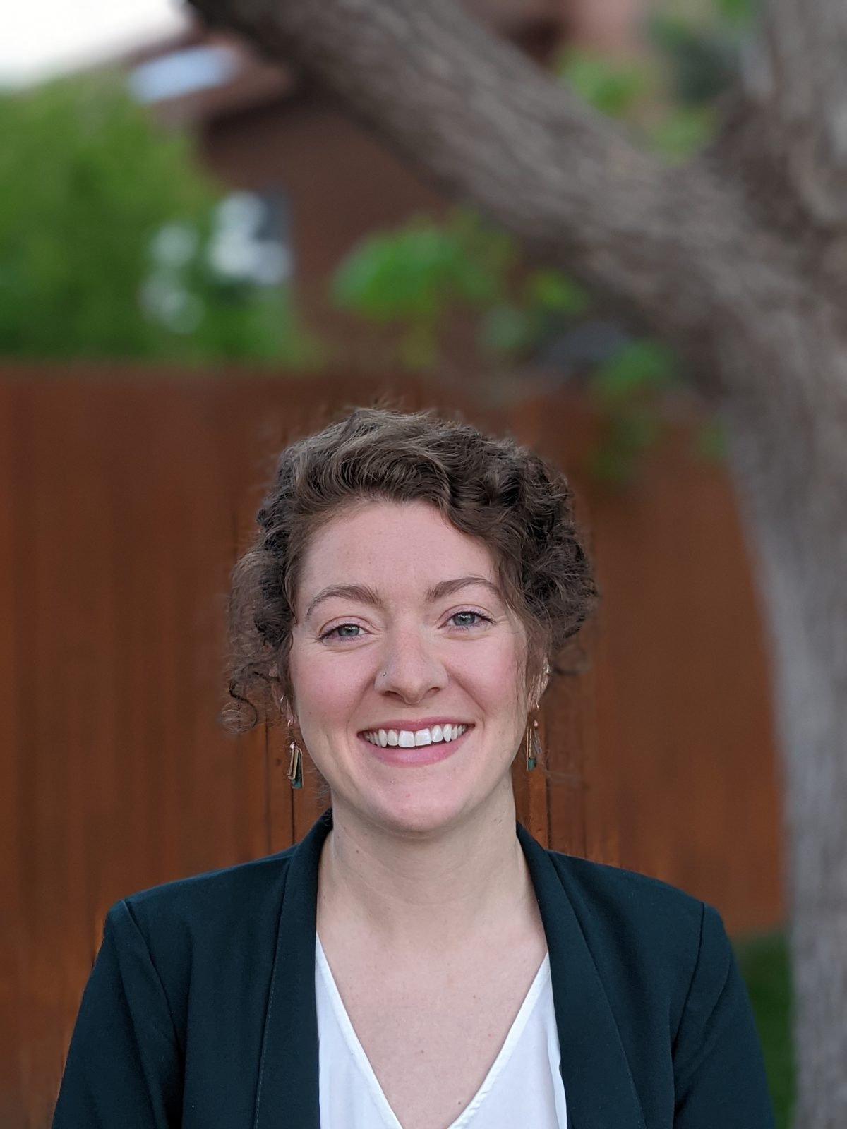 Picture of Molly O'Hara. Molly is a person with pale skin and brown curly hair which is short. She is wearing earrings, a dark blazer, and a white shirt. She is smiling. The background is blurry but shows a tree and the side of a building.
