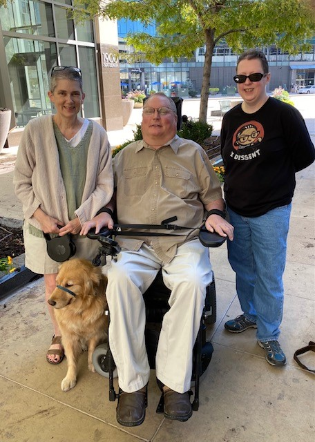 Amy, Tim, Martie, and Holly (dog) smiling together. Amy is a white woman with short gray hair. Tim is a white man with short hair and glasses in a wheelchair. Martie is a white woman with short dark hair and sunglasses. Holly is a golden retriever.